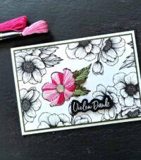 fadengrafik auf einer Karte mit einer gestickten Blume auf Papier