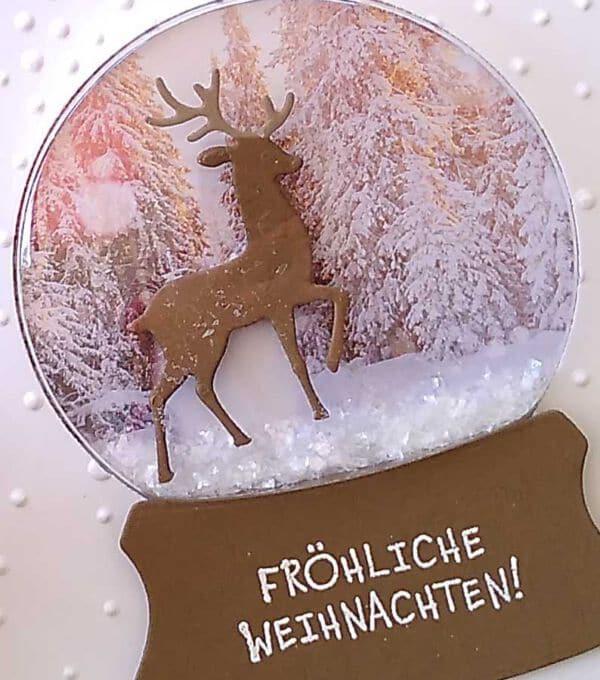 schuettelkarte mit hirsch im wald und schneekugel zu weihnachten
